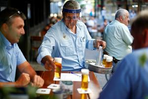 A bartender in Cologne wears a face shield while serving beer