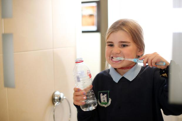 Emma Purcell (8) uses bottled water to brush her teeth at her home in north Co Dublin