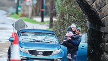 A motorist carries his child through flood water after his car got stuck on the Piltown Road in Bettystown, Co Meath