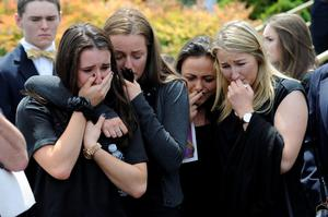 Mourners cry as the caskets of cousins Olivia Burke, 21, and Ashley Donohoe, 22, are placed in hearses following services at St. Joseph Catholic Church in Cotati, California on Saturday, June 20, 2015. (AP Photo/Michael Short