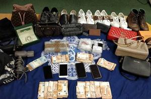 Some of the designer clothes and cash seized in the raid