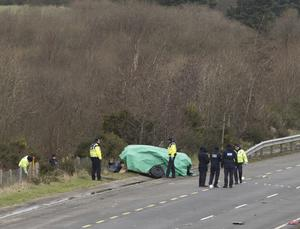 Gardai investigate a collision between two cars on the M1 at Carrickarnan in Co Louth where three people died