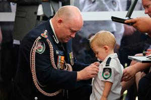 Nineteen-month-old Harvey Keaton has the honour pinned to his shirt during the funeral of his father Geoffrey
