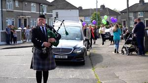 A lone piper leads the cortege for Robyn's funeral mass