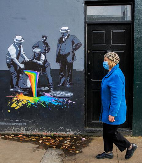A member of the public passes a mural on Clanbrassil Street as hopes for an easing of restrictions were raised
