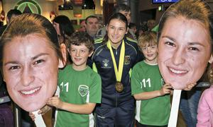 Katie Taylor pictured with fans, brothers, Gearoid (9) and Oisin (8) Murphy from Greystones at Dublin Airport this evening after arriving home after winning her fifth World Title in Korea