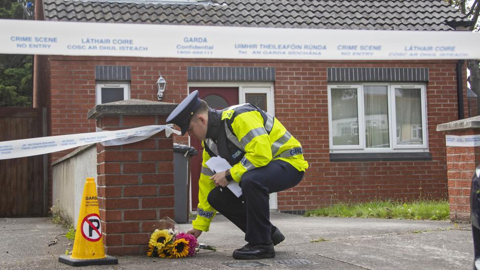 A garda lays flowers at the scene