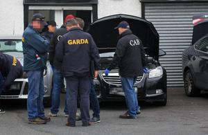 CAB officials and gardaí search cars at a Dublin dealership in a previous raid as part of a crackdown on 'The Family' gang
