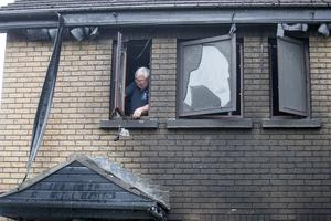 A workman at the blackened window