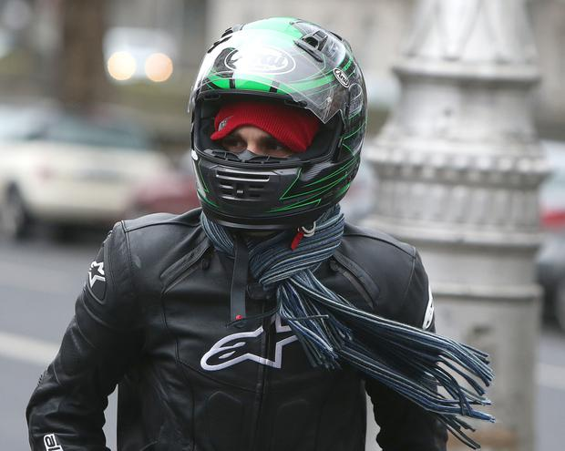 Christian at a previous court date wearing a motorcyle helmet