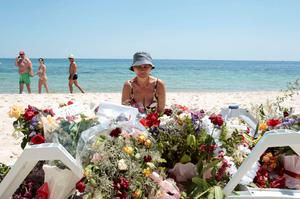 A tourist sits near flowers placed at the beachside of the Imperial Marhaba resort, which was attacked by a gunman in Sousse, Tunisia, June 28, 2015. Hundreds of armed police patrolled the streets of Tunisia's beach resorts on Sunday and the government said it will deploy hundreds more inside hotels after the Islamist militant attack in Sousse that killed 39 foreigners, mostly Britons. REUTERS/Zoubeir Souissi