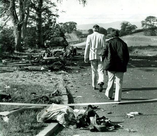 Personal belongings of the Miami showband members lie in the foreground as police officers examine the scene of the ambush of the band's minibus on the road between Banbridge and Newry in 1975