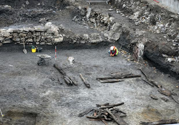 Archaeologists carefully excavate the site