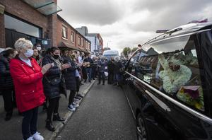Mourners in the inner city applaud as the coffin of Fergus McCabe passes by