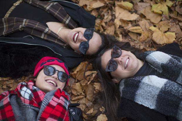 Monike Martins, Herika Martins and Leticia Pintoni, from Brazil, enjoy the sun in St Stephen's Green