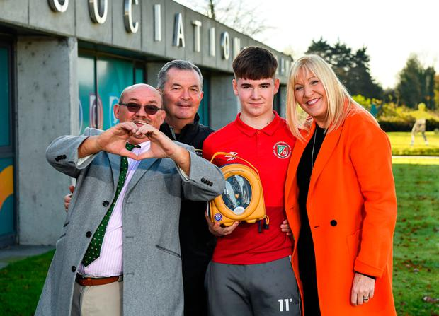 Brendan O'Carroll, left, and Jenny Gibney, right, with James O'Connell, centre, one of 85 young footballers successfully referred for cardiology assessment and treatment, and Alan Byrne, FAI Medical Director & Senior Men's Team Doctor, at FAI Headquarters in Abbotstown