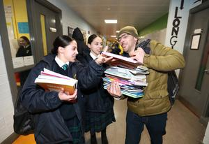 Ayoub Amer helps his twins, Rayhana and Ikram collect their books at Colaiste Bride