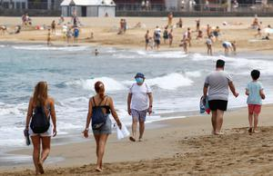 People walk on Las Canteras beach in Gran Canara as some Spanish provinces are allowed to ease lockdown restrictions during phase two