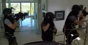 Footage released by police showed officers smashing down the doors of the luxury mansion before taking the Irishman away in handcuffs and seizing a gun