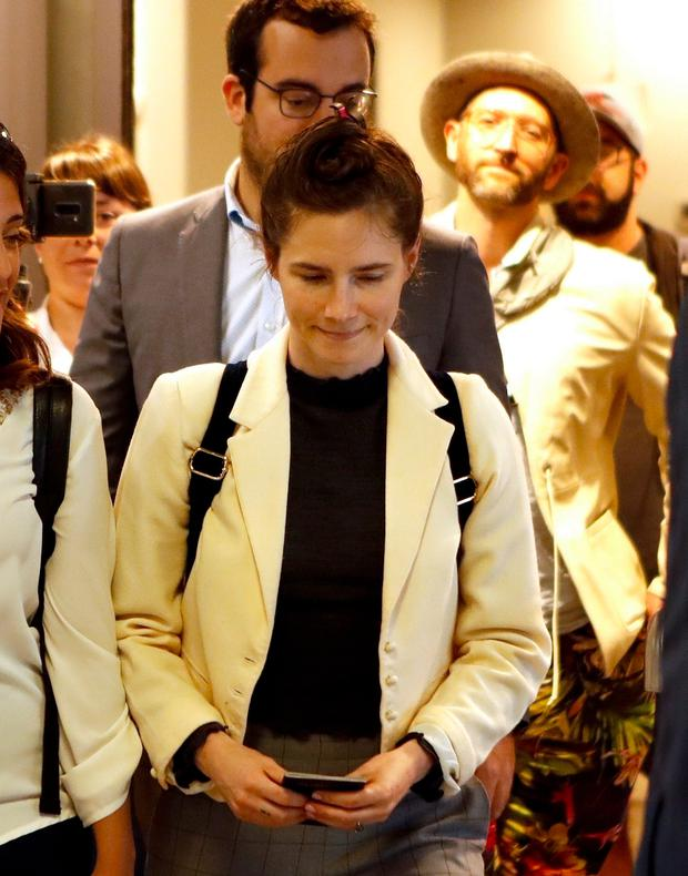 Amanda Knox exits Milan's Linate Airport via a side door only to face a media scrum