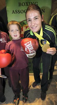 Katie Taylor pictured with Liam MacIonnraic (7) from Dublin and at Dublin Airport this evening after arriving home after winning her fifth World Title in Korea.. Picture Colin Keegan, Collins Dublin.