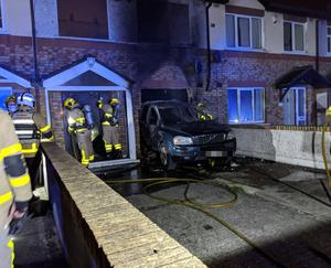 Firefighters at the house that had a car crashed into it and set alight