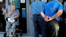 A elderly man In a wheelchair waits with other pensioners outside a national bank branch to withdraw a maximum of €120 ($134) for the week in central Athens