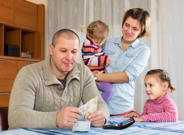 Smiling father with banknotes sitting at table, family staying nearby