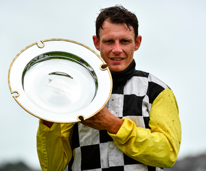 Jockey Paul Townend lifts the Guinness Plate after winning on Great White Shark