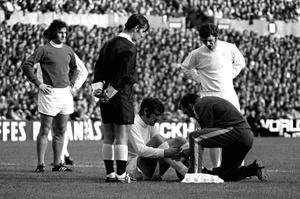 FRIENDS: John Giles looks on as Leeds United team-mate Norman Hunter receives attention.