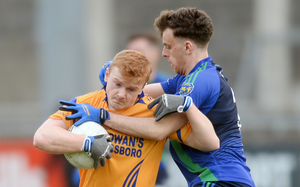 TIGHT MARKING: Conor McHugh of Na Fianna is tackled by Andrew Cunningham of St Sylvesters