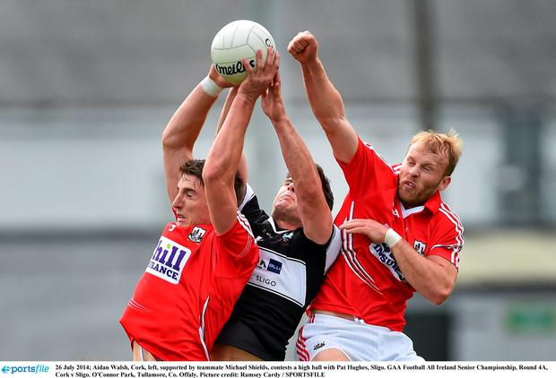 Cork's Aidan Walsh (left) and Michael Shields contest a high ball with Sligo's Pat Hughes. Picture credit: Ramsey Cardy / SPORTSFILE