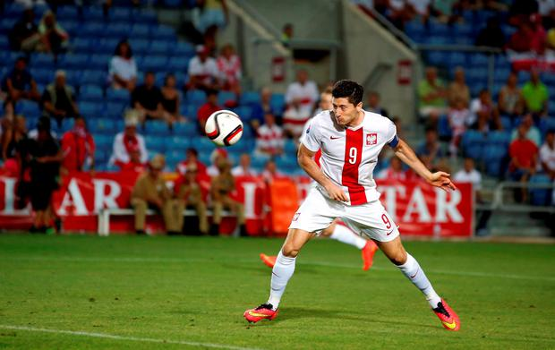 Poland's Robert Lewandowski heads the ball to score his goal against Gibraltar during their Euro 2016 qualification match at Algarve stadium in Faro