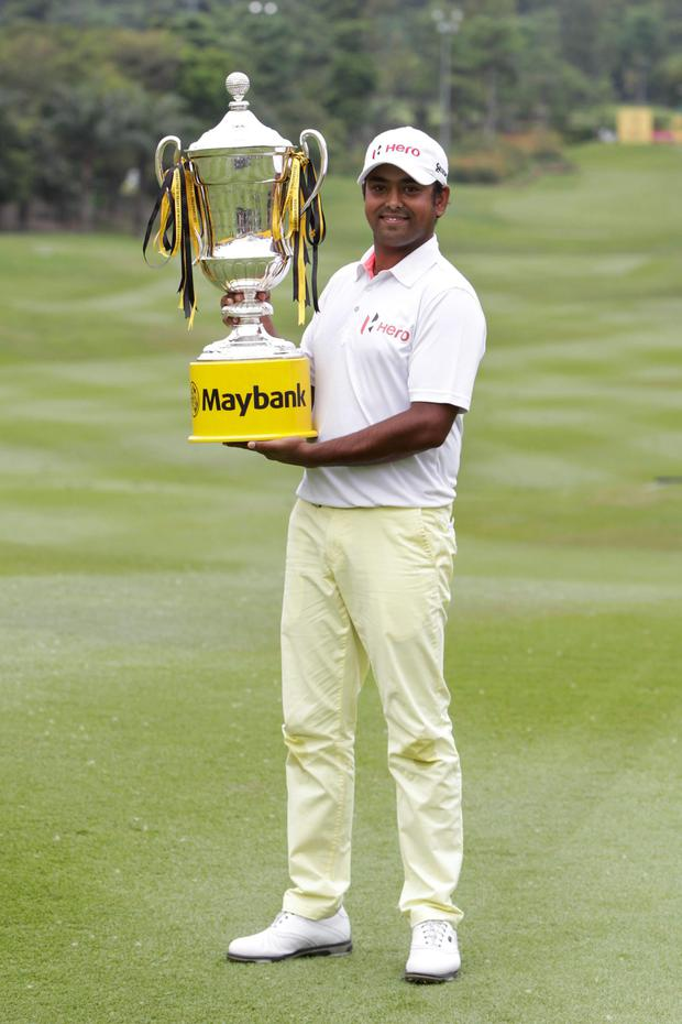 Anirban Lahiri of India poses with his trophy for photographers after winning the Malaysian Open golf tournament at Kuala Lumpur Golf