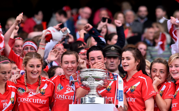 Cork captain Ashling Thompson, centre, celebrates with her team-mate's after being presented with the O'Duffy cup