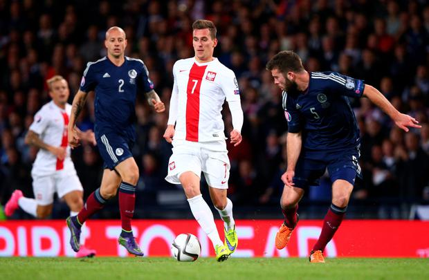 Arjkadiusz Milik of Poland takes on Grant Hanley of Scotland