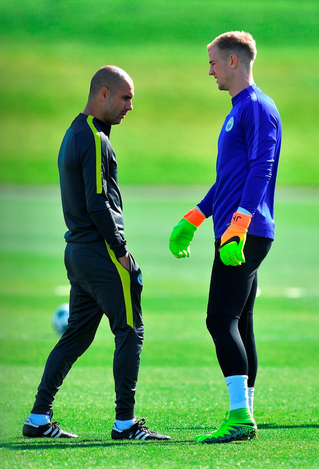 Manchester City manager Pep Guardiola talks to goalkeeper Joe Hart during a training session at the City Football Academy, Manchester yesterday. Photo: PA