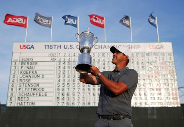 Brooks Koepka holds up the Golf Champion Trophy after winning the U.S. Open Golf Championship in Southampton, N.Y. AP Photo/Carolyn Kaster