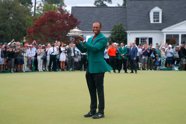BACK ON TOP: Tiger Woods celebrates with with his green jacket and trophy after winning the 2019 US Masters at Augusta National Golf Club yesterday. Photo: REUTERS/Brian Snyder
