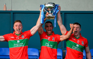 Ballymun Kickhams captain James McCarthy (centre) lifts the Clerys Perpetual Cup alongside Paddy Small (l) and John Small after the Dublin SFC final at Parnell Park