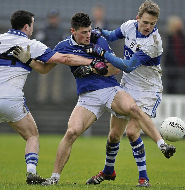 Ciaran Dorney, left, and Tomas Quinn of St Vincent's converge on Shane Flynn of St Loman's. Picture: Pat Murphy / SPORTSFILE