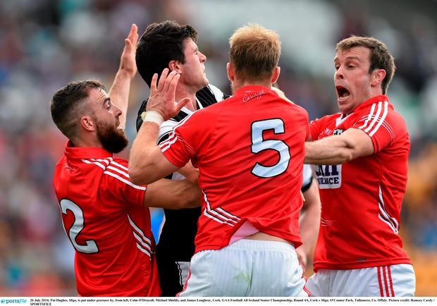 Pat Hughes, Sligo, is put under pressure by, from left, Colm O'Driscoll, Michael Shields, and James Loughrey, Cork. Picture: Ramsey Cardy/SPORTSFILE