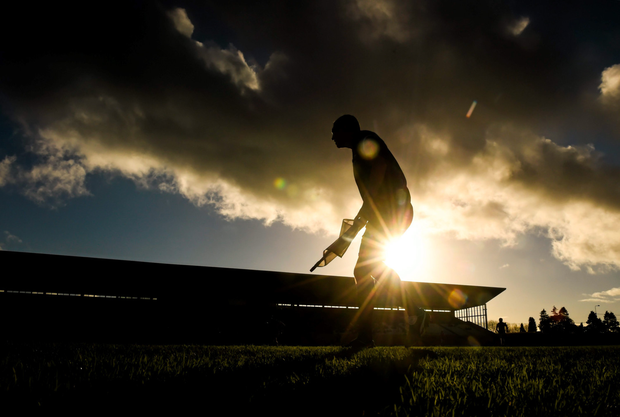 A linesman watches play as the winter sun sets during the AIB Leinster Senior Club Hurling Championship quarter-final between Coolderry and Cuala in Tullamore