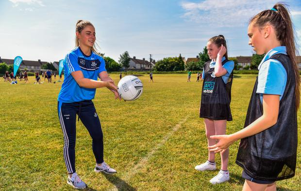 LEARNING THE SKILLS: Dublin's Aoife Kane (l) passes a ball to Halle McDonald (r) with Kim Ellis at the AIG Heroes event in Ballyfermot
