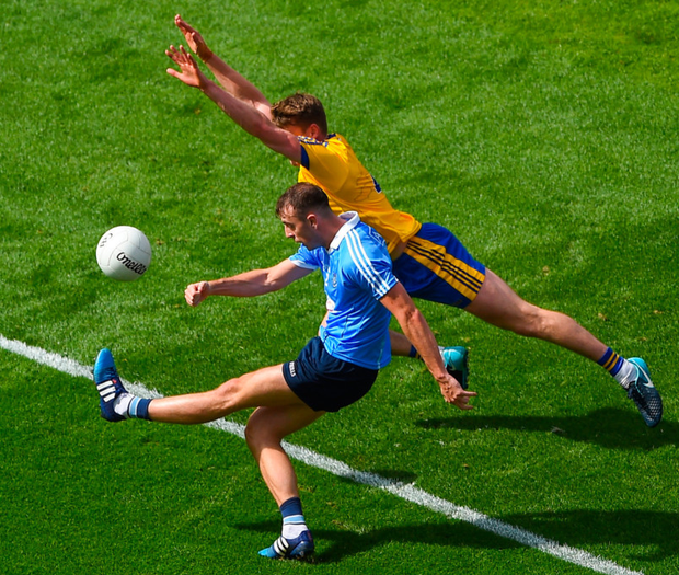 IT'S OVER: Dublin's Cormac Costello slots a point off his left foot as Roscommon's Niall McInerney tries to block him down. Photo: Sportsfile