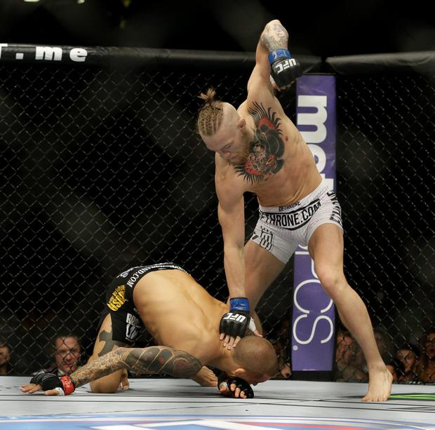 Conor McGregor hits Dustin Poirier during their featherweight mixed martial arts bout at UFC 178