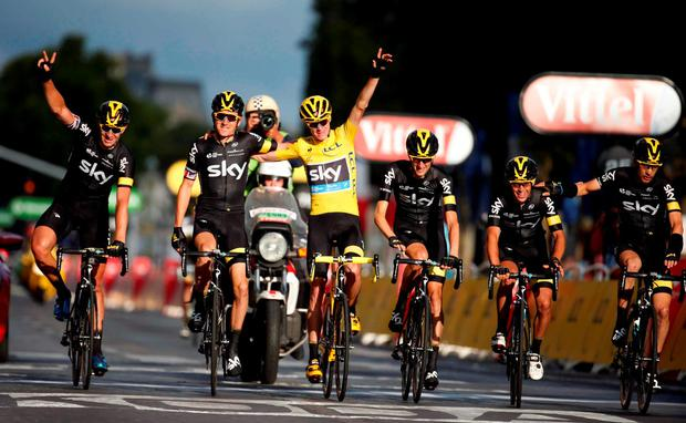 Team Sky rider Chris Froome (c) celebrates his overall victory with team-mates after the 109.5-km (68 miles) final stage of the 102nd Tour de France