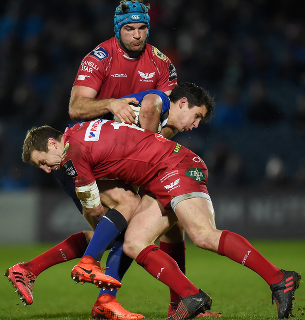 Leinster's Joey Carbery is tackled by Scarlets' Hadleigh Parkes (front) and Tadhg Beirne during their PRO12 match at the RDS in March