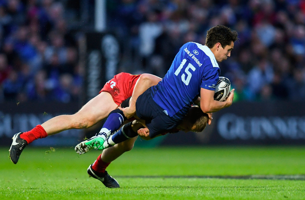 Joey Carbery of Leinster is tackled by James Davies of Scarlets
