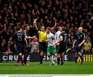 14 November 2014; Stephen Quinn, Republic of Ireland, receives a yellow card from referee Milorad Mazic after players from both sides clashed. UEFA EURO 2016 Championship Qualifier, Group D, Scotland v Republic of Ireland, Celtic Park, Glasgow, Scotland. Picture credit: David Maher / SPORTSFILE
